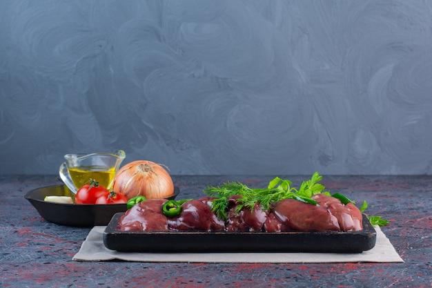 Zwarte plaat van rauwe lever met verse groenten op marmeren oppervlak