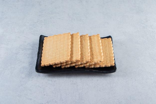 Zwarte plaat van smakelijke koekjes geplaatst op stenen achtergrond.