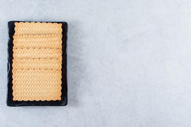 Zwarte plaat van smakelijke koekjes op steen geplaatst.