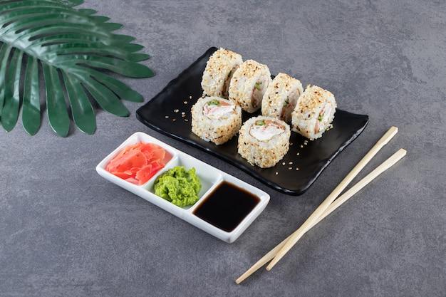 Zwarte plaat van sushi rolt met sesamzaadjes op stenen achtergrond.