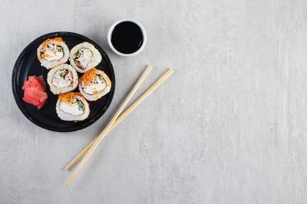 Zwarte plaat van sushibroodjes met spaanders en krab op steenachtergrond.
