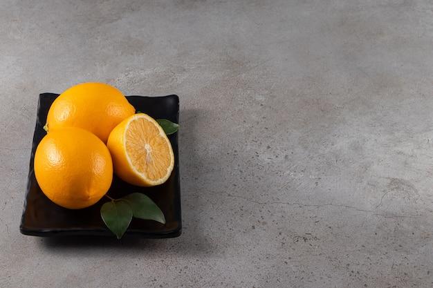 Zwarte plaat van verse, sappige citroenen op stenen achtergrond.