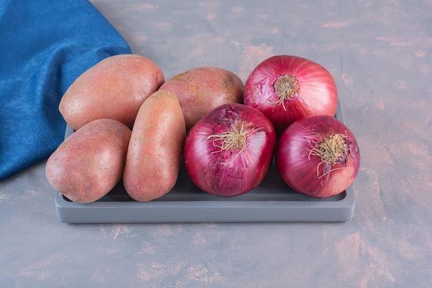 Zwarte plaat van zoete aardappelen en rode uien op stenen achtergrond.