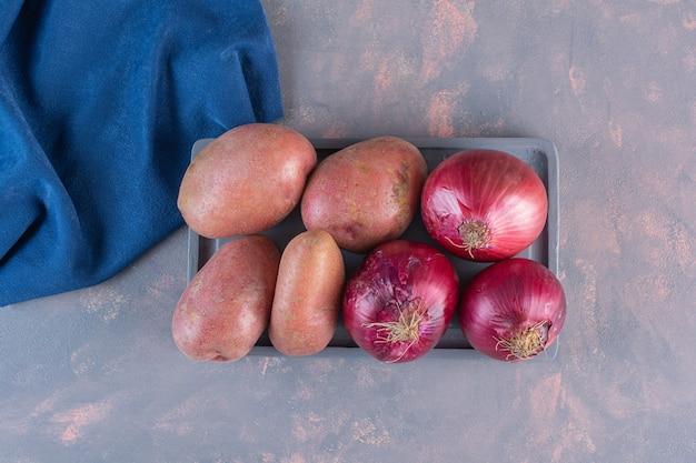 Zwarte plaat van zoete aardappelen en rode uien op stenen oppervlak