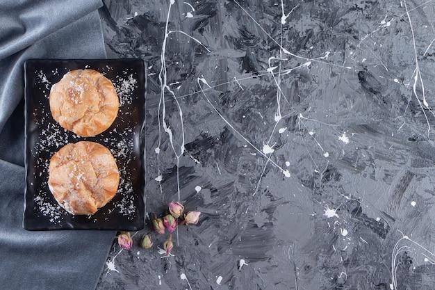 Zwarte plaat van zoete soesjes met slagroom op marmeren tafel.