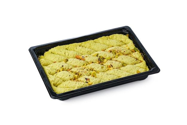 Zwarte plastic doos van turks halva-dessert dat op witte achtergrond wordt geïsoleerd
