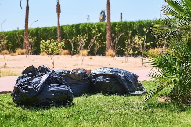 Zwarte plastic zakken met afval op het gras