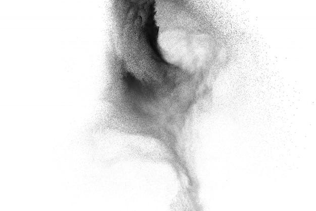 Zwarte poederexplosie tegen witte achtergrond. houtskoolstofdeeltjes ademen uit in de lucht.