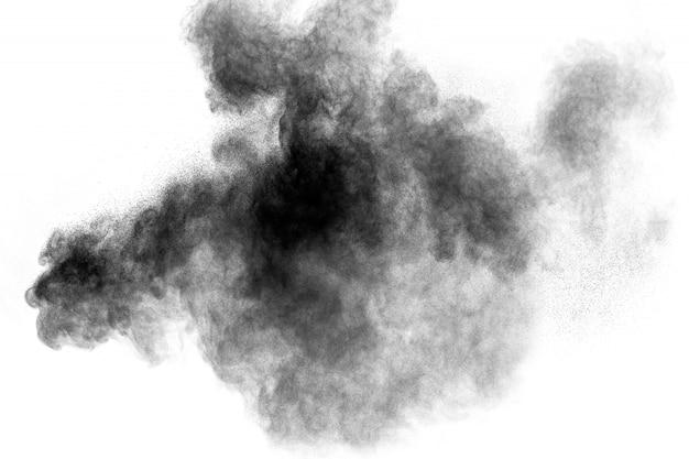 Zwarte poederexplosie tegen witte achtergrond. houtskoolstofdeeltjes wolkelen in de lucht.