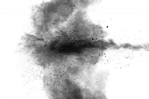 Zwarte poederexplosie tegen witte achtergrond. zwarte stofdeeltjes spatten.