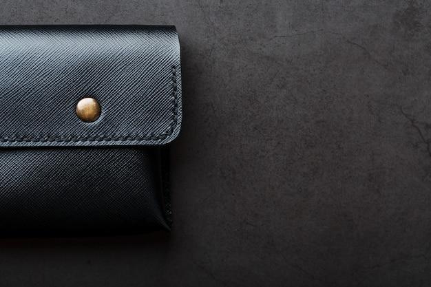 Zwarte portemonnee gemaakt van echt leer op donker