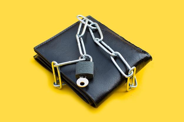 Zwarte portemonnee in kettingen gesloten hangslot op gele ondergrond