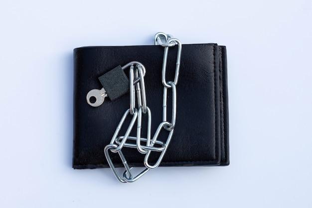 Zwarte portemonnee in kettingen gesloten hangslot op wit oppervlak