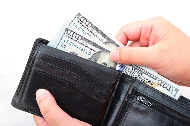 Zwarte portemonnee met amerikaanse dollars in de handen op een witte achtergrond