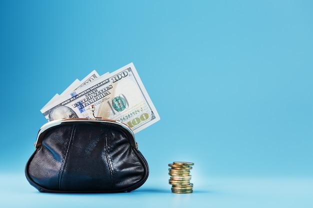 Zwarte portemonnee met munten en dollars op blauw.