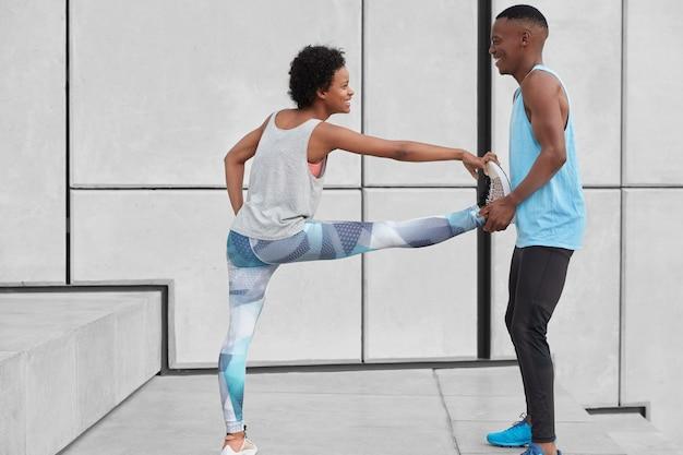 Zwarte positieve mannelijke instructeur helpt vrouwelijke stagiair oefeningen te doen voor flexibiliteit, bij trappen tegen een witte muur te staan, blije uitdrukkingen te hebben, gekleed in sportkleding. mensen, sport en training concept