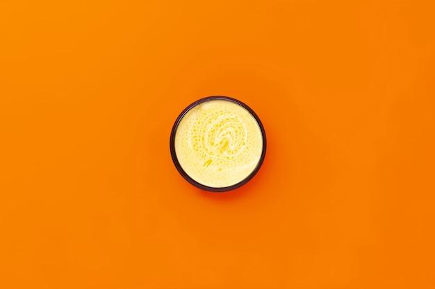 Zwarte pot met gele room met duindoornolie op een sinaasappel