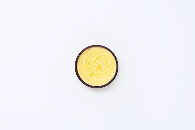 Zwarte pot met gele room met duindoornolie op een wit