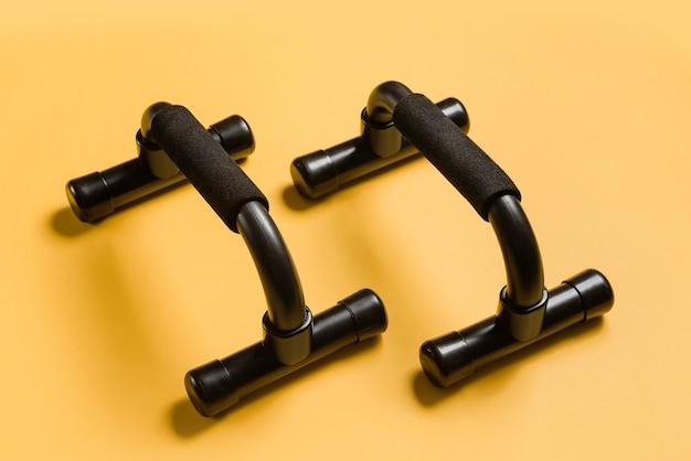 Zwarte push-up bars op een gele muur close-up. trainingsapparatuur voor thuis.