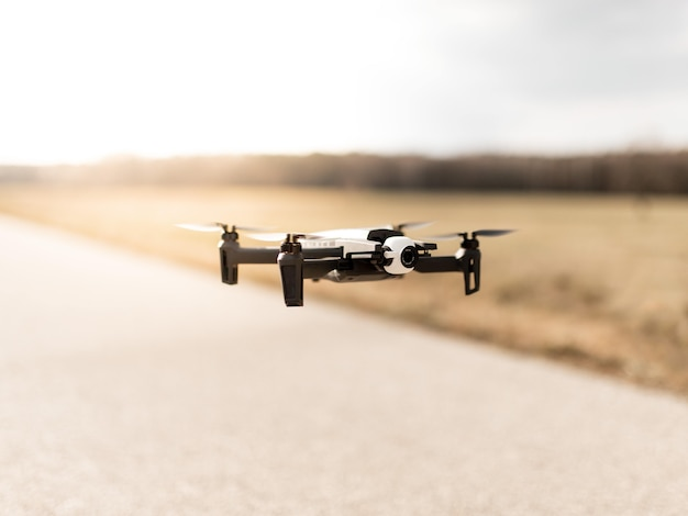 Zwarte quadcopter drone over een bewolkte hemel