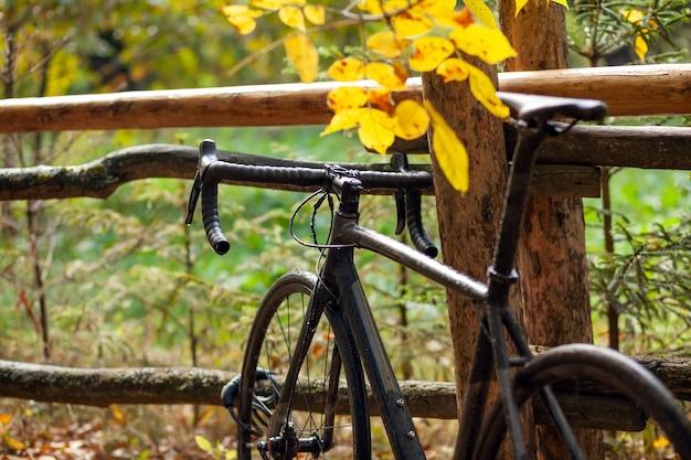 Zwarte racefiets geparkeerd in de buurt van het oude houten hek in het herfstpark. regenachtig bewolkt weer
