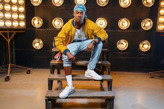 Zwarte rapper in glb zittend op de trap, zanger op het podium met schijnwerpers op de muur. rapperformer op scène met lichten, undergroundmuziek, stedelijke stijl