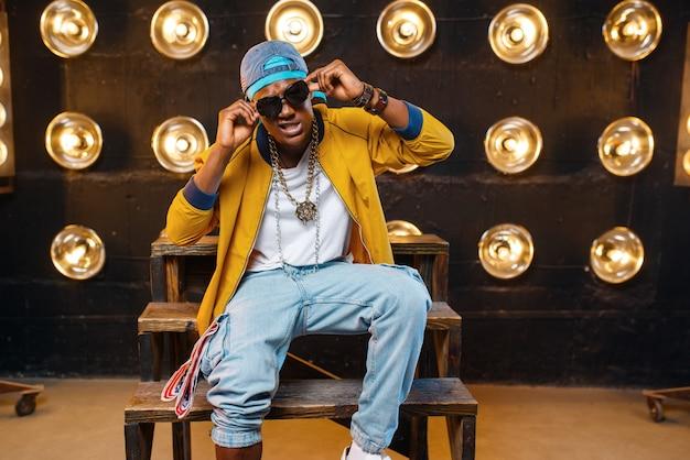 Zwarte rapper in pet en zonnebril zittend op de trap, zanger op het podium met schijnwerpers op de muur. rapperformer op scène met lichten, undergroundmuziek, stedelijke stijl