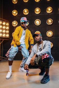 Zwarte rappers in petten dansen op het podium met schijnwerpers