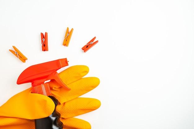 Zwarte reinigingsspray ter beschikking in oranje handschoen en veelkleurige wasknijpers op witte achtergrond. reiniging, netheid en huishoudelijke chemicaliën concept. kopieer ruimte