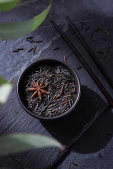 Zwarte rijst in een zwarte kom op een leisteen bord op een zwarte achtergrond