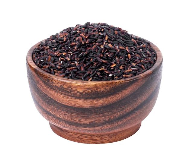 Zwarte rijst in houten kom die op wit wordt geïsoleerd