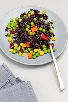 Zwarte rijst met groenten in grijze plaat. grijze achtergrond. bovenaanzicht