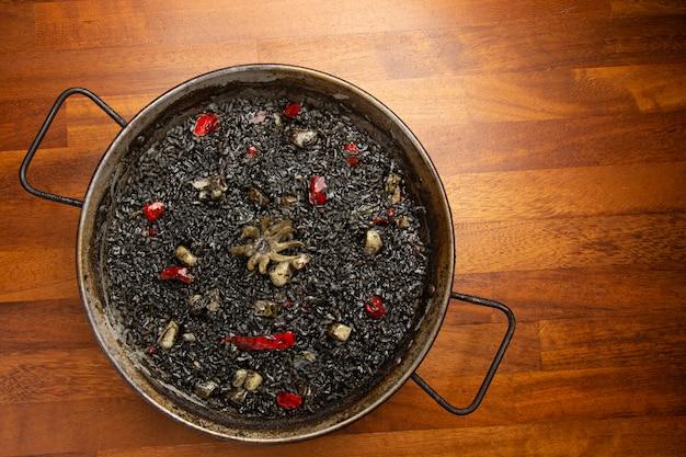 Zwarte rijst met inktvis in paella pan op hout