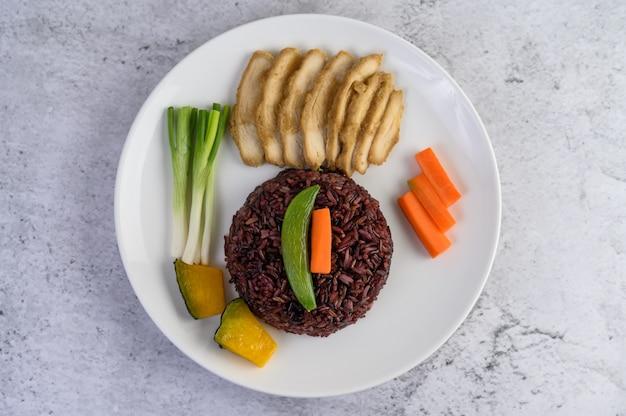 Zwarte rijst op een bord met pompoen, erwten, wortelen, baby maïs en gestoomde kipfilet.