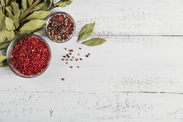 Zwarte, rode en witte peperkorrels en gedroogde laurierblaadjes op witte houten achtergrond