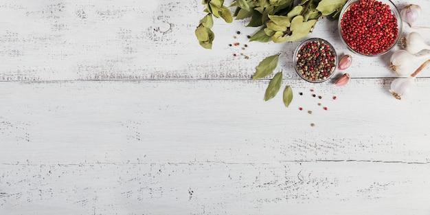 Zwarte, rode en witte peperkorrels, gedroogde laurierblaadjes en knoflook op witte houten achtergrond