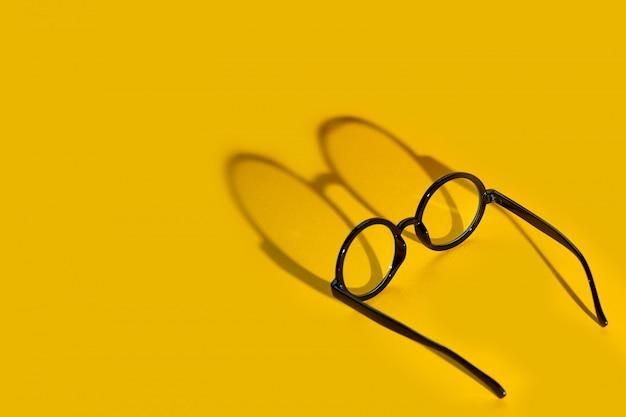 Zwarte ronde bril op een gele achtergrond met harde schaduw en de inscriptie look