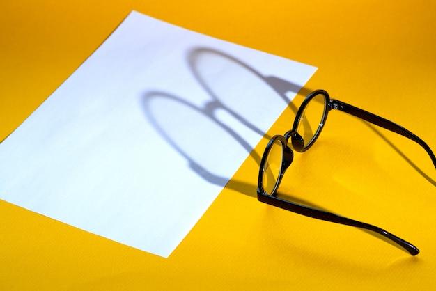 Zwarte ronde bril op een gele achtergrond met harde schaduw en het opschrift ziet eruit
