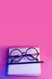 Zwarte ronde glazen liggen op een notitieblok in neonlicht op roze