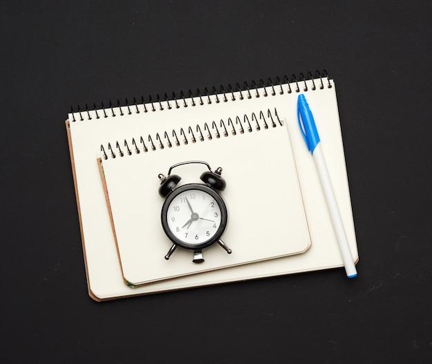 Zwarte ronde klok en stapel spiraalvormige open notitieboekjes met lege witte bladen op een zwarte
