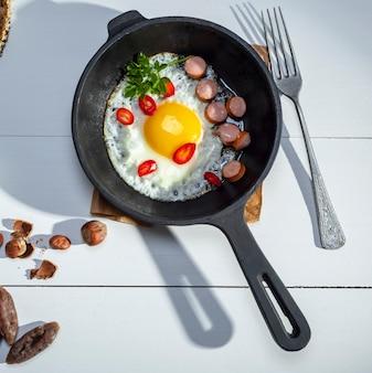 Zwarte ronde koekenpan met gebraden kippenei en worsten