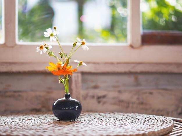 Zwarte ronde vaas met bloemboeket op vintage houten tafel in de buurt van glazen raam in woonkamer bij zonsondergang.