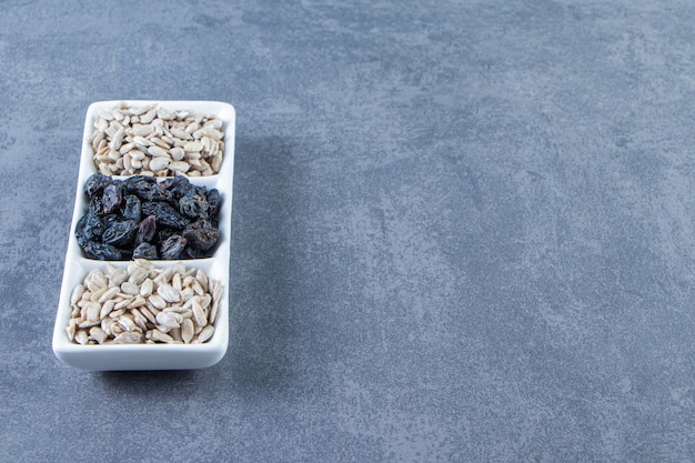 Zwarte rozijnen en gepeld zaad in een schotel, op de marmeren achtergrond.