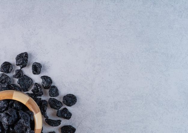 Zwarte rozijnen in een houten beker op betonnen ondergrond.