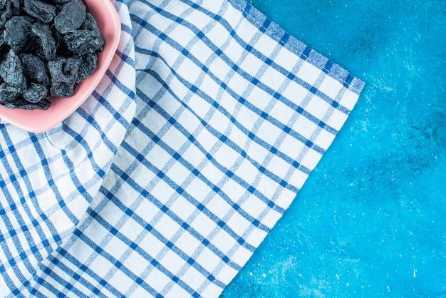 Zwarte rozijnen in een kom op theedoek, op de blauwe tafel.