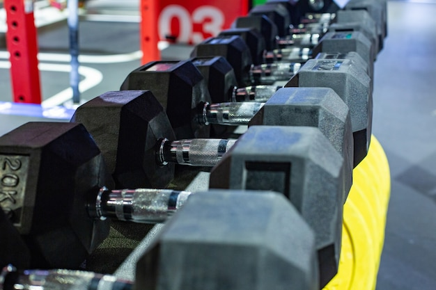 Zwarte rubberen halters. zeshoekige heavy-duty gewichtset die wordt gebruikt voor serieuze hardcore gymtrainingen, cross-fit training en workoutroutines