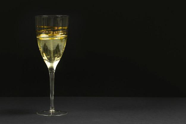 Zwarte scène met een glas champagne.