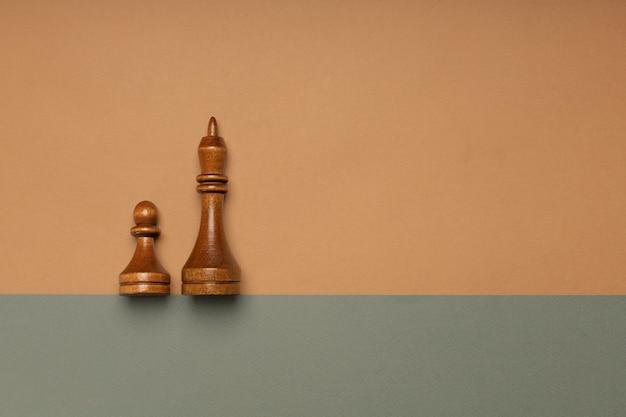 Zwarte schaakpion en koning op vlakke achtergrond