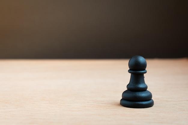 Zwarte schaakpion met zwarte achtergrond