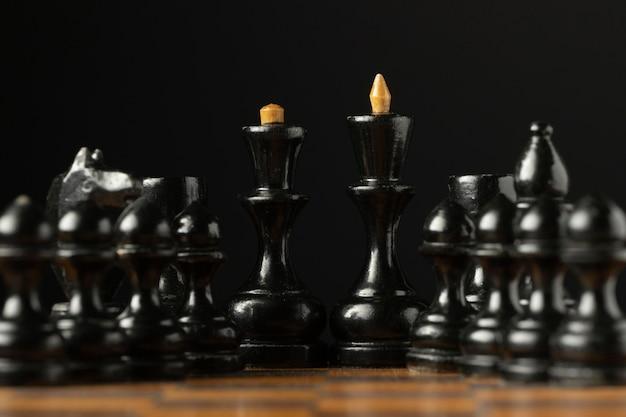 Zwarte schaakstukken op schaakbord. koning en koningin stukken.